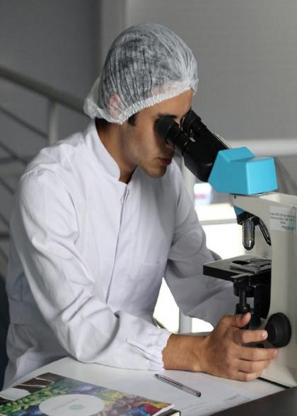 White clothed man looking into microscope